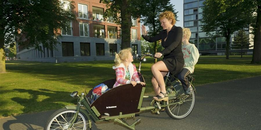 Werkende moeder brengt haar kinderen in een bakfiets naar school.