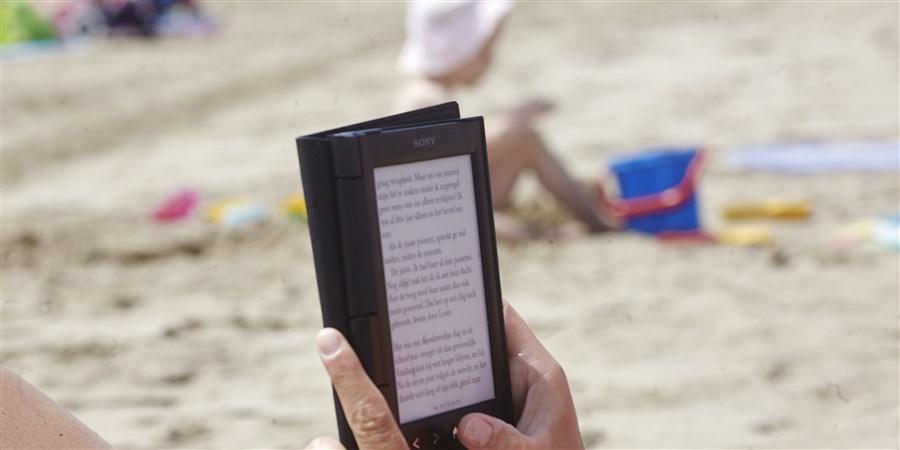 Op voorgrond leest iemand een e-reader, op achtergrond strand met spelend kind