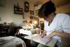 Wijkverpleegkundige op bezoek bij patiënt thuis vult papieren in