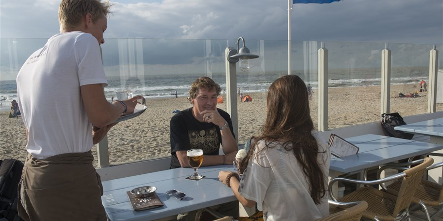 Strandtent, bediening van een jongen van bijna 16 jaar, in de zomer