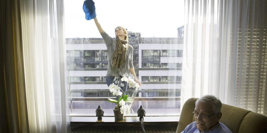 Foto dame wast raam bij bejaarden man