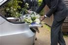 Mannen leggen rouwboeketten in een lijkwagen.