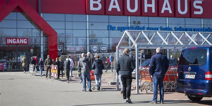 Bezoekers staan in verband met corona op afstand van elkaar bij ingang van bouwmarkt te wachten