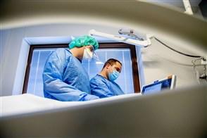 Een arts en een verpleegkundige met mondkapjes aan het werk op de intensive care