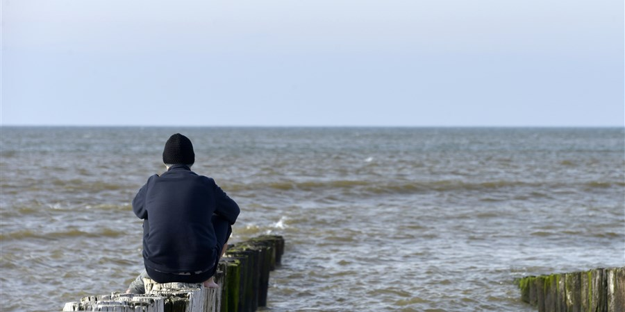 Een man zit op een golfbreker en kijkt naar zee