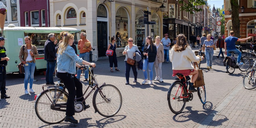 Voetgangers en fietsers zoeken hun weg in het oude centrum van Utrecht. Op sommige plaatsen in de stad is anderhalve meter afstand nauwelijks haalbaar.