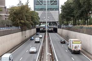 Twee wegen die naast elkaar lopen onder een viaduct door.
