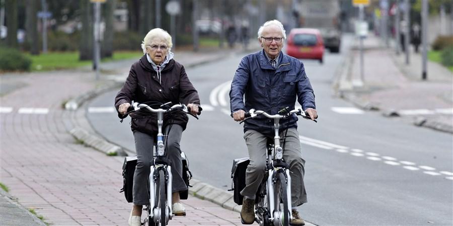 Bejaard echtpaar fietst op fietspad