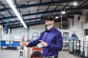 Company employee wearing VR goggles in shop floor