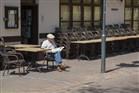 Oudere man zit de krant te lezen op een leeg terras
