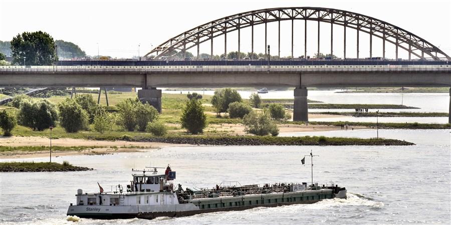 Een binnenvaartschip passeert de nevengeul in de waal ter hoogte van Nijmegen .