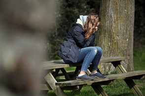 Meisje zit alleen op een picknicktafel en kijkt somber voor zich uit