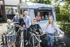 Gezin met acht kinderen poseren met fietsen voor een caravan.