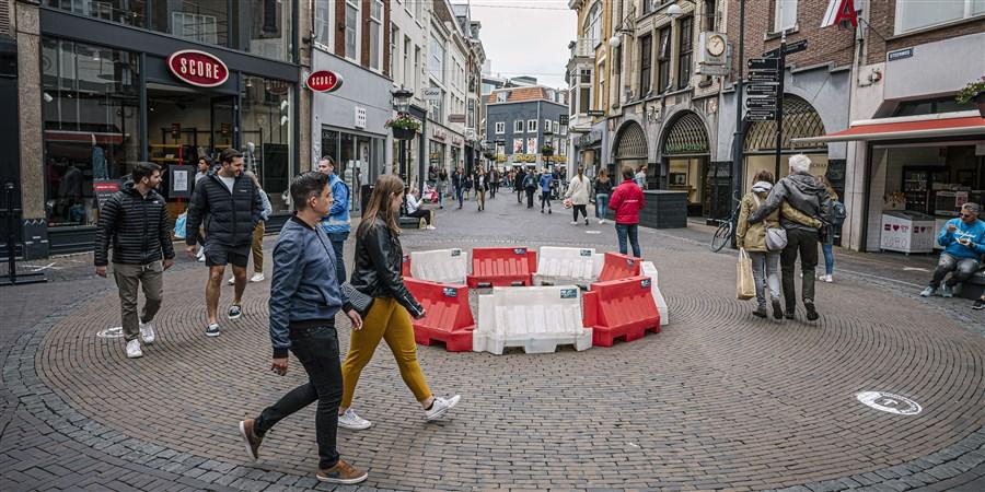 Het winkelpubliek loopt in het centrum van Utrecht langs een rotonde.
