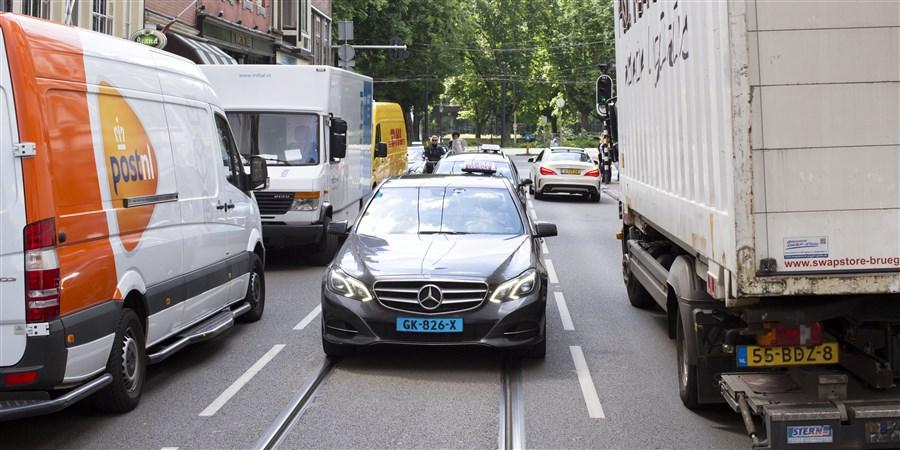Taxi rijd in een druk straat in de stad.