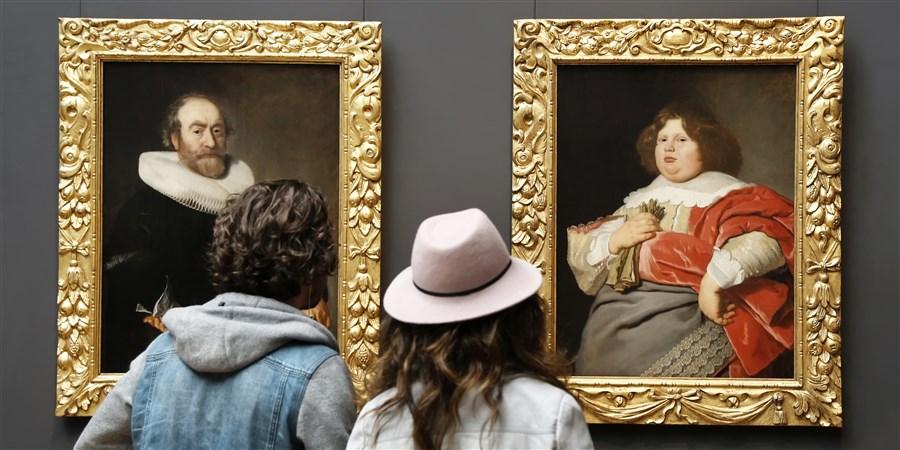 2 bezoekers kijken naar schilderijen met daarop dikke mensen