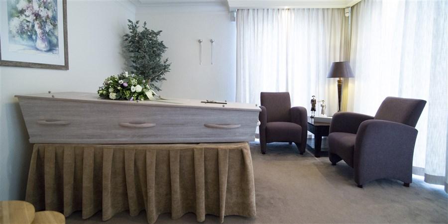 Een overzichtsfoto van een kamer in huiselijke sfeer in een uitvaartcentrum