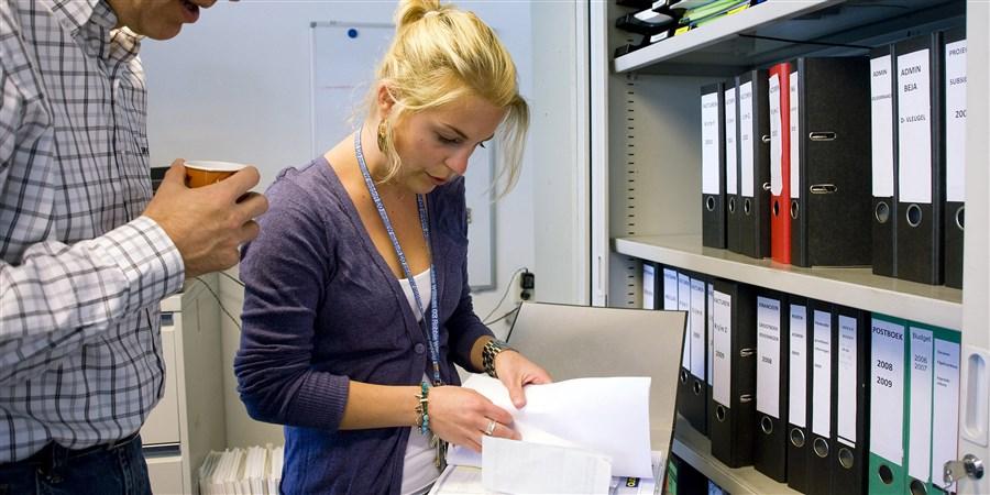Jonge vrouw op haar kantoor met ordner in overleg met collega.