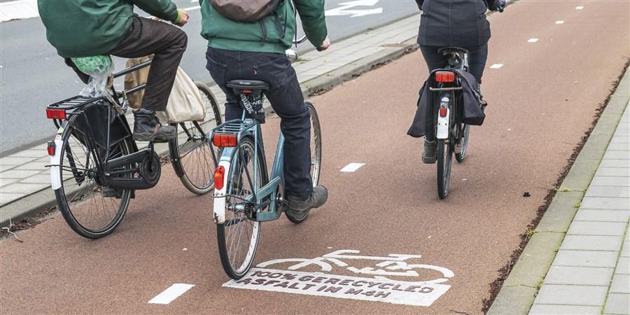 Drie fietsers op een fietspad gemaakt van 100% gerecycled asfalt