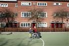 kleinzoon op inline skates achter de roelstoel van opa op sportveld in woonwijk