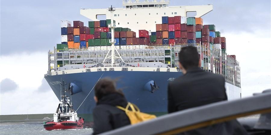 Mensen kijken naar enorm containerschip dat in de rotterdamse haven binnen komt