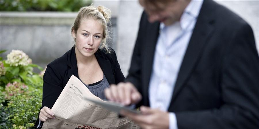 Twee collega's. Een man en een vrouw. De vrouw leest de krant, hij zit op zijn mobiel. Zij kijkt naar hem, wat hij aan het doen is.