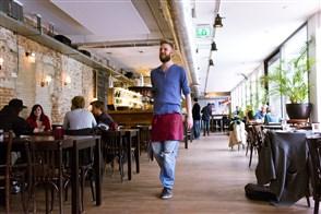 jonge ober met een dienblad met drinken in een horecagelegenheid