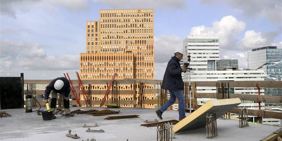Twee bouwvakkers aan het werk op een gebouw aan de Amsterdamse Zuidas