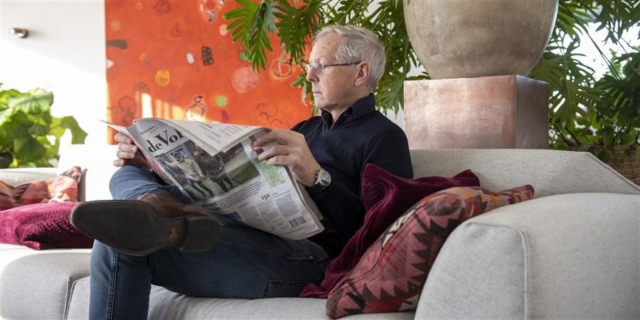 Man in huiskamer leest de krant op de bank