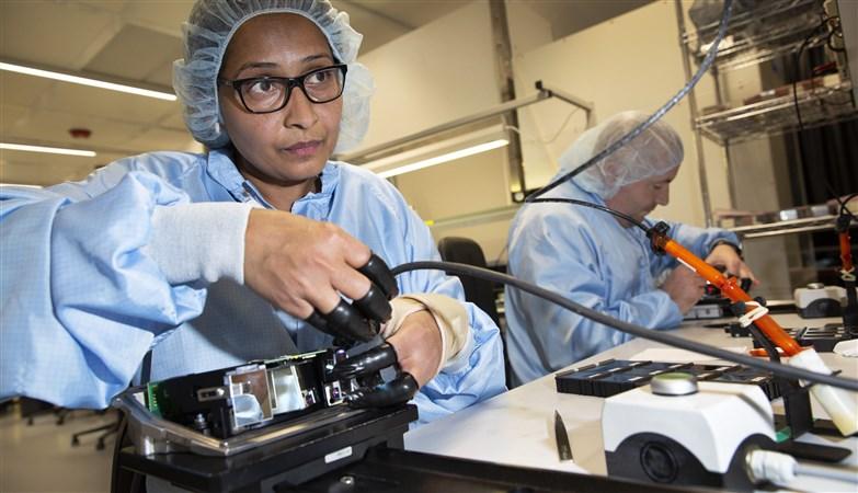 Een medewerker verlijmd een de spiegel in de scanner van een melkrobot.
