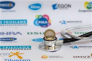 Stethoscoop met 1-euromunt met op de achtergrond logo's van zorgverzekeraars
