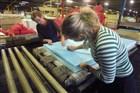 Arbeidskrachten verwerken schuimrubber tot een matras in een schuimrubberfabriek.
