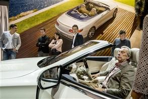 Bezoeker van een lifestylebeurs test de zit van een luxe model cabriolet (uit de 500-serie)