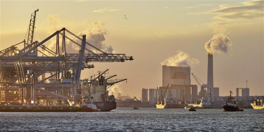Containerhaven met schepen en electriciteitscentrale op de achtergrond