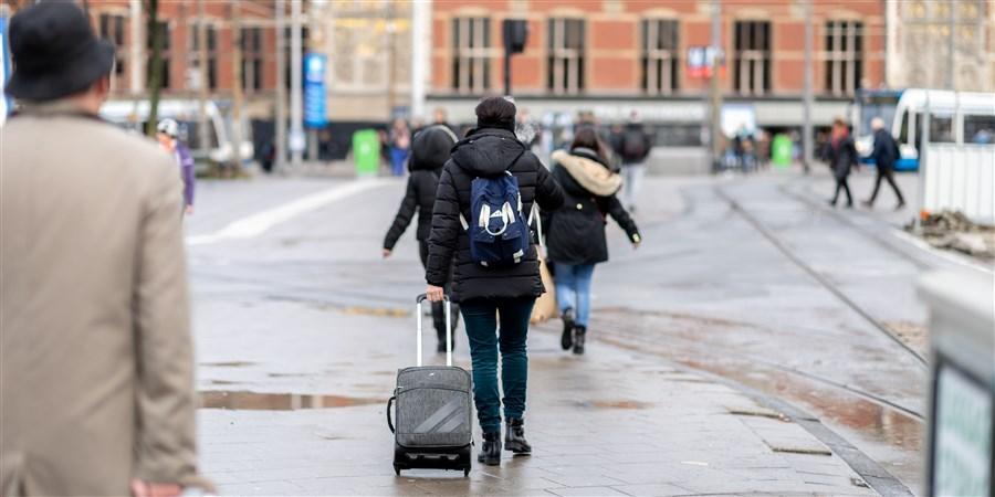 een toerist die met zijn koffer naar Amsterdam centraal loopt