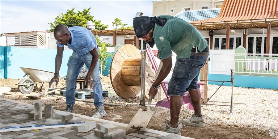 Twee bouwvakkers bestraten een weg op Bonaire