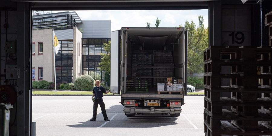 Een man staat bij een vrachtwagen voor een laadplatform