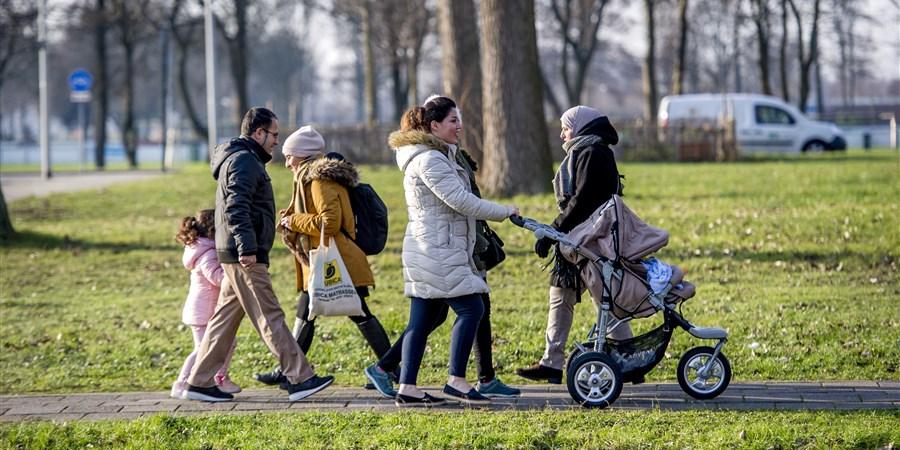 Asielzoekers,  lopend op een stoep.
