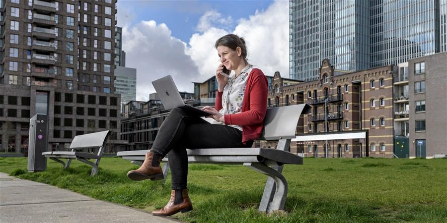 Vrouw zit met haar laptop op een bankje te werken
