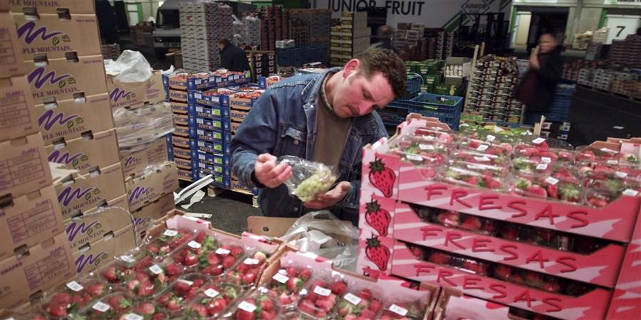 man bekijkt druiven in groentehandel