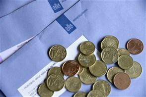 Envelop van de Belastingdienst met  daarbovenop kleingeld