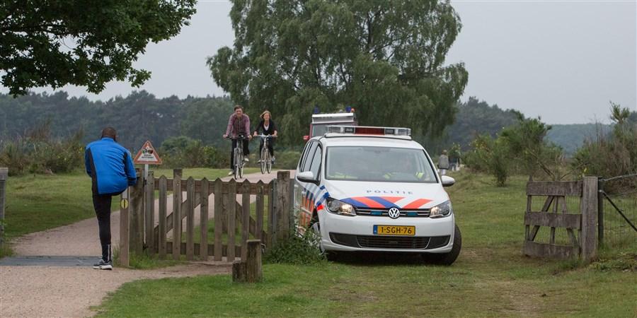 Politieauto bij hek dat toegang geeft tot de westerheide