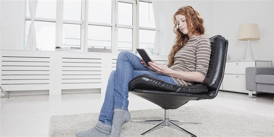 Meisje met ereader in een stoel in een moderne huiskamer