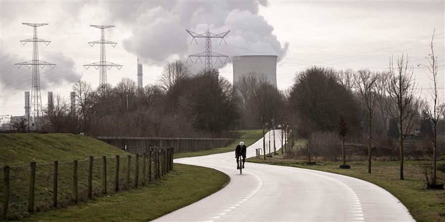 Een wielrenner met op de achtergrond de Clauscentrale in Maasbracht