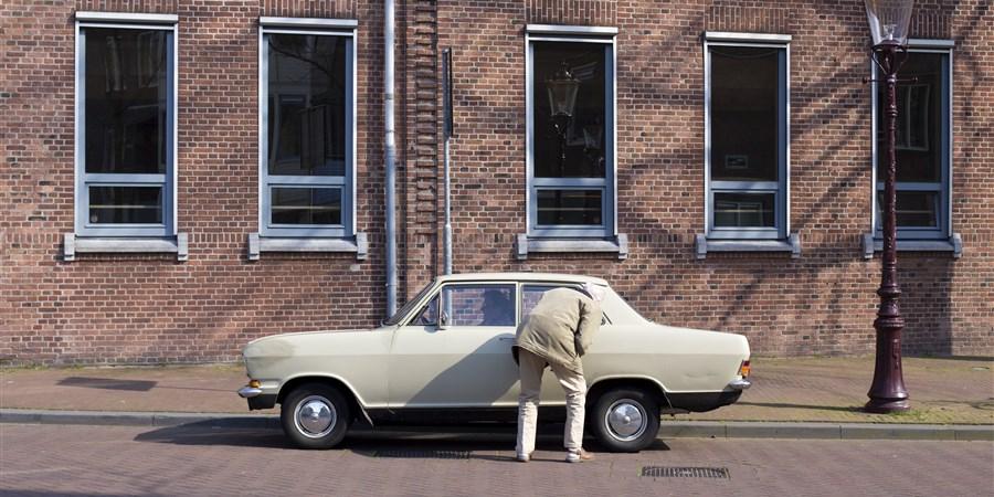 Oude man bij zijn oude auto