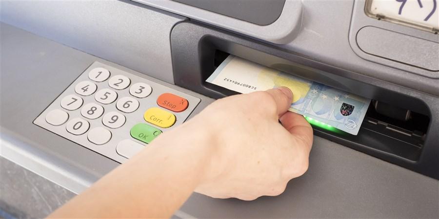 Persoon pakt geld uit geldautomaat