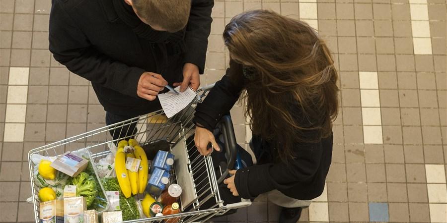Klanten met boodschappenlijstje en winkelwagen