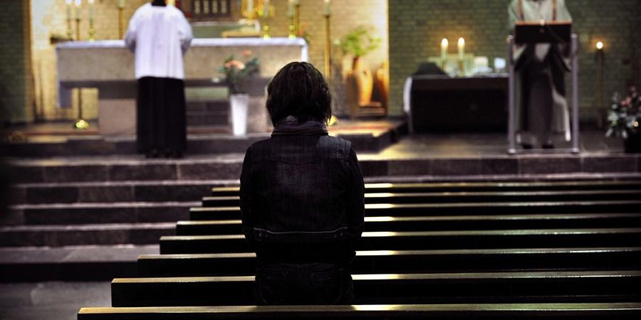 Katholieke kerkdienst, priesters en gelovige biddend in beeld