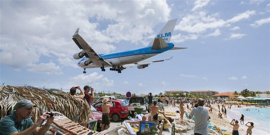 Vliegtuig komt heel laag over strand heen