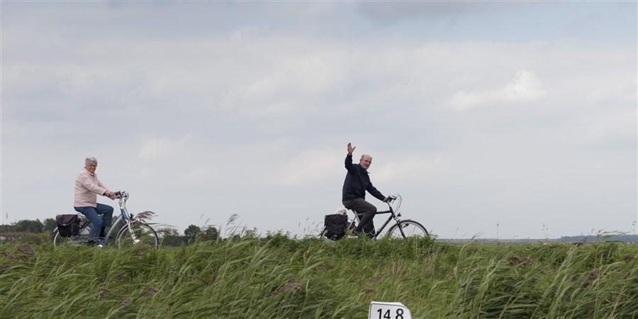Ouder stel op de fiets. Man zwaait richting de fotograaf.